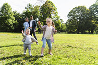 Happy family playing with soap bubble in a park - UUF13809