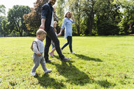Happy family walking hand in hand in a park - UUF13812