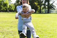 Happy mother lifting up son in a park - UUF13815
