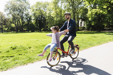 Happy father riding bicycle with daughter in a park - UUF13818