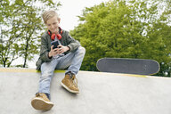 Boy with headphones in skatepark using smartphone - PDF01635