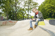 Boy with headphones in skatepark using smartphone - PDF01638