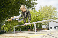 Boy jumping over railing in skatepark - PDF01644