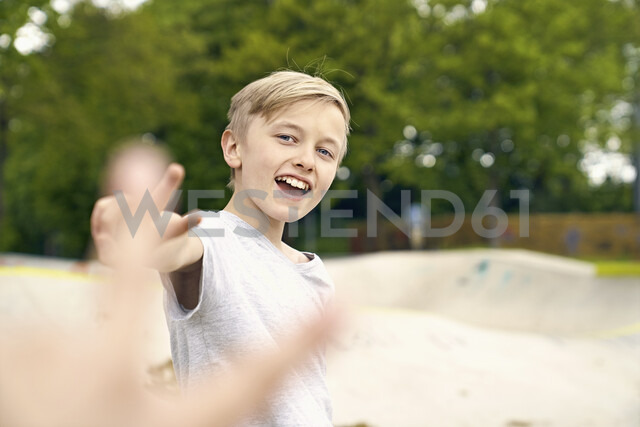 Boy doing victory sign in skatepark - PDF01653