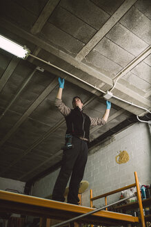 Man working on conduit at the ceiling - RAEF02051