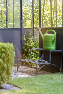 Germany, greenhouse and green watering can - MMAF00345