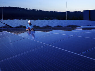 Worker with measuring device checking solar plant in the evening - CVF00536