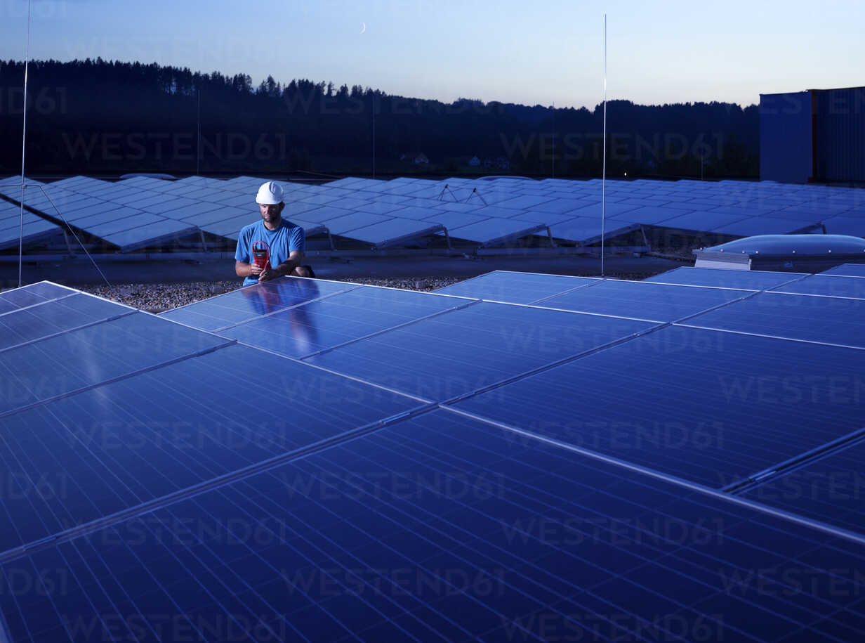 Worker with measuring device checking solar plant in the evening - CVF00536 - Christian Vorhofer/Westend61