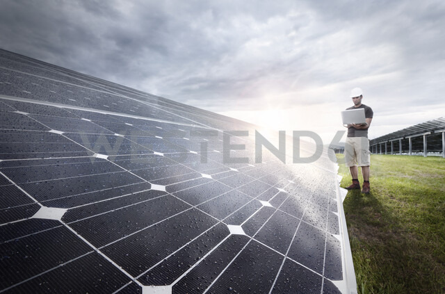 Engineer with laptop checking solar plant at evening twilight - CVF00539
