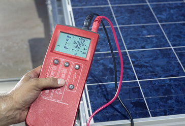 Man's hand holding measuring device in front of solar plant, close-up - CVF00542