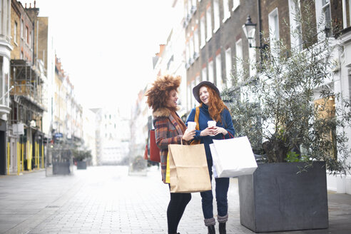 Two young women standing in street, holding shopping bags and coffee cup - CUF09284