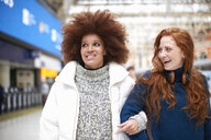 Two young women at train station, walking arm in arm - CUF09290