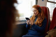 Woman on train listening to music on mobile phone with headphones, London - CUF09293