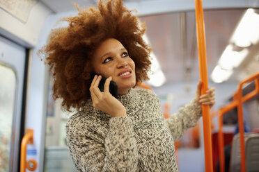 Woman using mobile phone on train, London - CUF09296