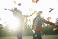 Friends throwing autumn leaves in air - CUF09311