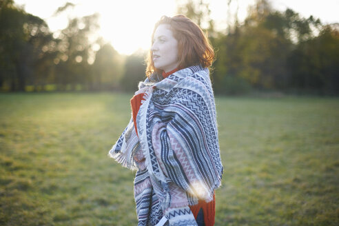 Young woman in rural setting, wrapped in blanket - CUF09332
