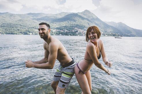 Portrait of couple in swimwear buttock to buttock in Lake Como, Lombardy, Italy - CUF09356
