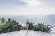 Rear view of young woman on viewing platform looking out at Lake Como, Lombardy, Italy - CUF09359