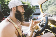 Young male hipster on road trip using smartphone navigation, Como, Lombardy, Italy - CUF09371