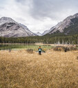 Woman standing, looking at view, rear view, Kananaskis Country; Bow Valley Provincial Park, Kananaskis, Alberta, Canada - CUF09611