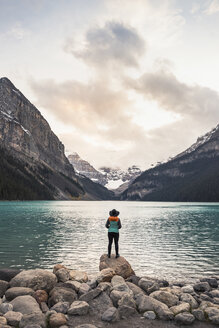 Woman standing on rock, looking at lake view, rear view, Lake Louise, Alberta, Canada - CUF09614