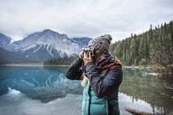 Woman taking photograph of view, Emerald Lake, Yoho National Park, Field, British Columbia, Canada - CUF09617