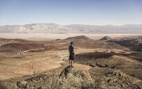 Man on rock looking out over Death Valley National Park, California, USA - CUF09620