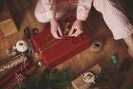 Woman wrapping christmas gift with twine - CUF09626