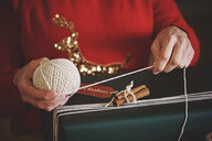 Woman wrapping christmas gift with twine - CUF09629