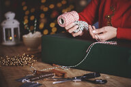 Woman wrapping christmas gift with twine - CUF09632