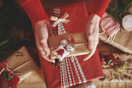 Cropped view of woman holding christmas present - CUF09638
