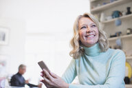 Smiling, confident mature woman using smart phone - HOXF03538