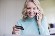 Smiling mature woman with credit card talking on telephone - HOXF03550