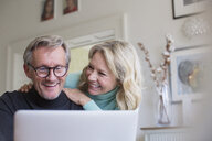 Smiling mature couple using laptop - HOXF03568