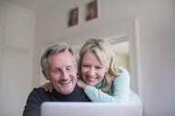 Smiling, happy mature couple using laptop - HOXF03583