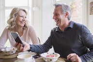 Laughing mature couple using smart phone and eating breakfast - HOXF03589