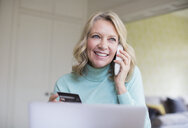 Smiling mature woman with credit card talking on telephone at laptop - HOXF03610