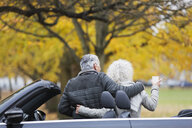 Senior couple with convertible at autumn park - CAIF20521