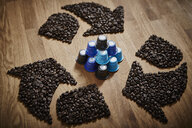 Coffee beans forming recycle symbol around plastic coffee pods - CAIF20536