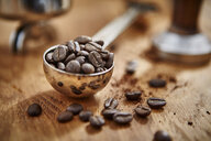 Close up roasted coffee beans in measuring cup scoop - CAIF20548