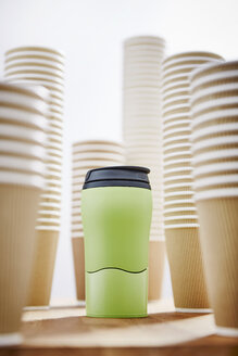 Green insulated drink container surrounded by disposable coffee cups - CAIF20551