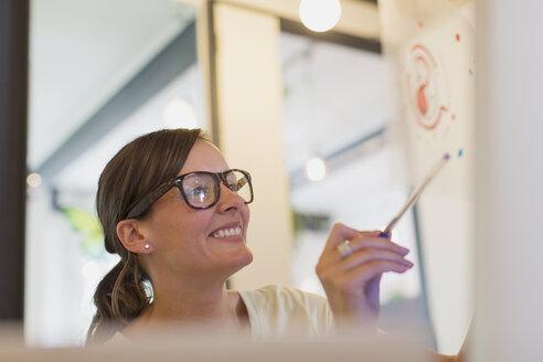 Smiling female designer examining transparency diagram - CAIF20599