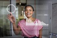 Smiling, enthusiastic businesswoman using futuristic hologram computer - CAIF20635