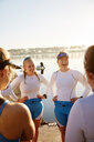 Female rowing team laughing and talking at sunny lakeside - CAIF20647
