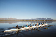 Female rowers rowing scull on sunny lake under blue sky - CAIF20665