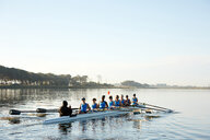 Female rowers rowing scull on lake below blue sky - CAIF20674