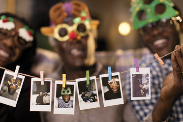 Portrait playful family in Christmas costume goggles showing instant photos - CAIF20680