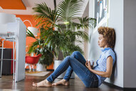 Young woman sitting on floor, taking a break - CUF09820