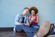 Young woman and boyfriend sitting on floor listening to earphone music - CUF09823