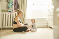 Pregnant woman and daughter in bedroom - CUF09871